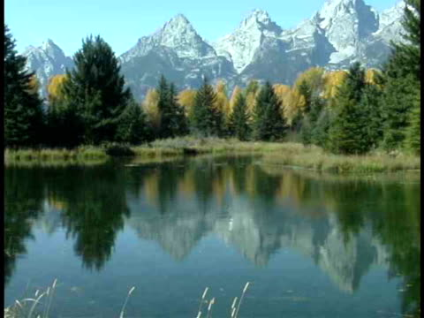 ms, tu, snow capped mountains by lake, grand teton national park, wyoming, usa - parco nazionale del grand teton video stock e b–roll