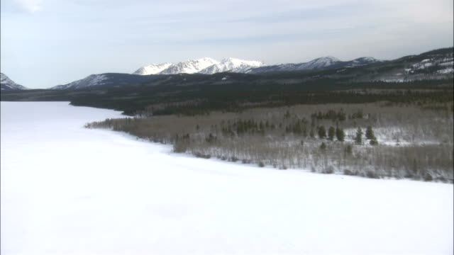 snow capped mountains rise near a frozen tagish lake. - whitehorse stock videos and b-roll footage