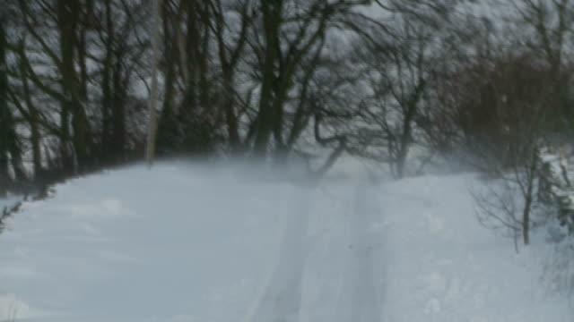 carlisle; snow covered country landscape / four wheel drive car along country road through snow / wind drifting snow / traffic along road... - 黒猫点の映像素材/bロール