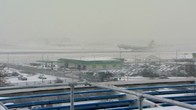 snow causes disruption across uk; heathrow: airplane barely seen through snow british airways plane taking off airport vehicle along with lights... - wide stock videos & royalty-free footage