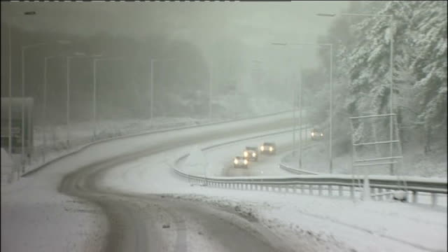 ext police car parked behind lorry jackknifed along central barrier on a470 police car with flashing lights police officer with shovel waving truck... - snow vehicle stock videos and b-roll footage