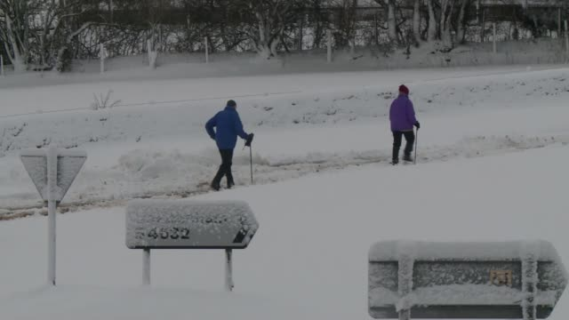 Gloucestershire Cars and buses stranded in snow at side of country road Couple with ski poles walking along through thick snow on road Wide shot of...
