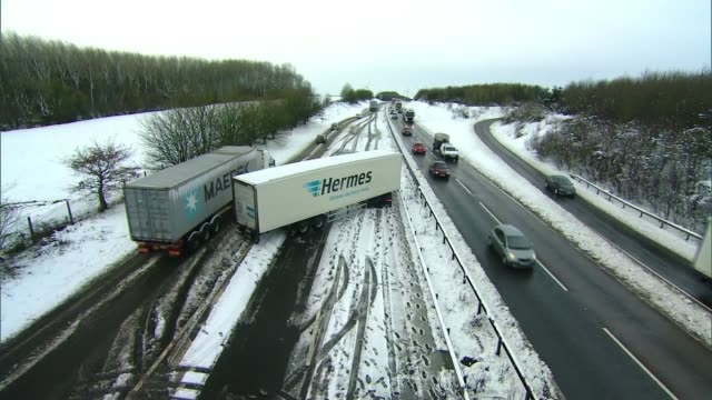 vídeos de stock e filmes b-roll de northamptonshire a14 lorry slewed across carriages on a14 traffic along a14 in snowy conditions slowmoving queue of lorries truck skidding in snow as... - vehicle breakdown