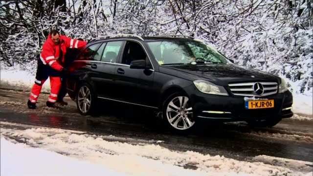 snow causes travel disruption; ext / snow mercedes car slipping as men try to push at through snow on road - pushing stock videos & royalty-free footage