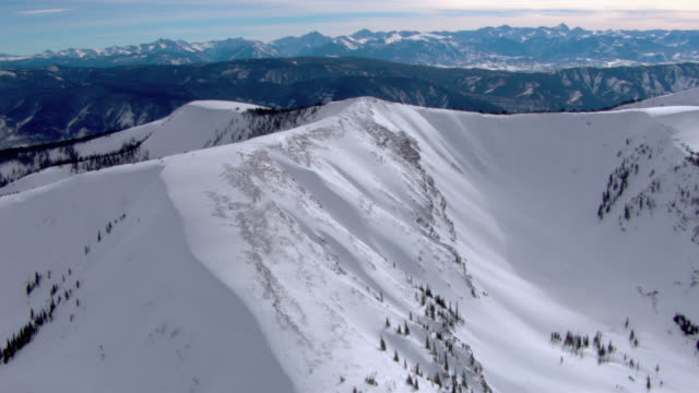 vidéos et rushes de snow clings to the sides and peaks of a mountain. - colorado