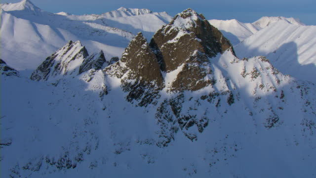 Snow clings to the sides of rugged rock formations atop mountains in the Yukon.