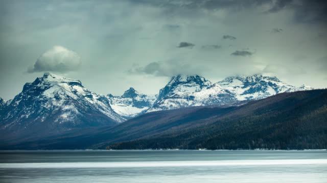 氷河国立公園の湖と山々に吹く雪雲 - タイムラプス - モンタナ州点の映像素材/bロール
