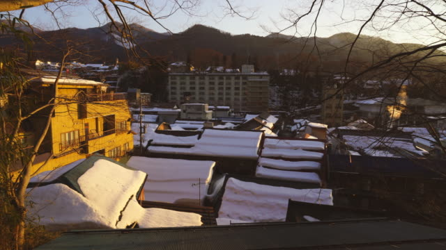 snow covered crowded rooftops among the shibu onsen town in sunset at shibu onsen (shibu hot spring) yamanouchi-machi, nagano japan on feb. 18 2019. - nagano prefecture stock videos and b-roll footage