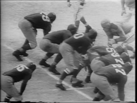 snow covered football field / men fork straw into a truck / bundled up fans in stands / players sit on bench with straw in front of them / players on... - 1945 stock videos & royalty-free footage