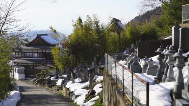 snow covered many gravestones at cemetery along the street at edge of town at shibu onsen (shibu hot spring) yamanouchi-machi, nagano japan on feb. 18 2019. - ryokan stock videos and b-roll footage