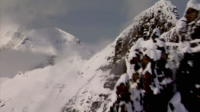 SLO MO, LOW AERIAL, Snow covered mountain ridge and clouds, Whitefish, Montana, USA