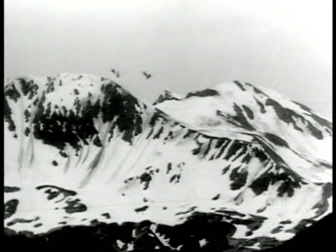 snow covered mountains w/ two small artillery puffs of smoke rising behind mountain allied soldiers walking in snow down mountain more soldiers can... - aleutian islands stock videos and b-roll footage