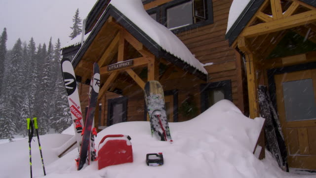 snow covered roof to skis snowboard skiing equipment partially buried in snow mound in front of ski lodge building on snowy day - ski lodge stock videos & royalty-free footage