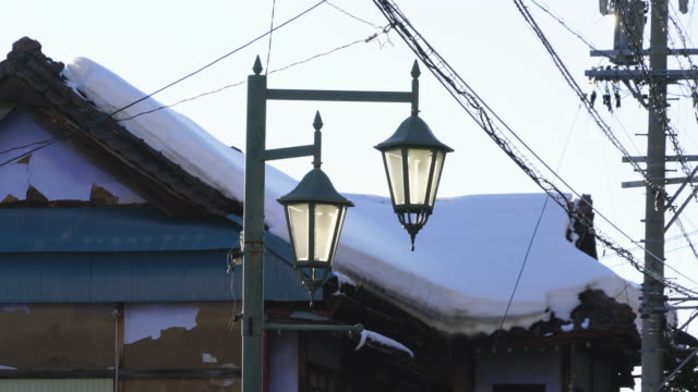 Snow covered rooftop of closed business Ryokan (Traditional Japanese Inn) behind the streetlights at Shibu Onsen (Shibu Hot Spring) Yamanouchi-machi, Nagano Japan on Feb. 17 2019.