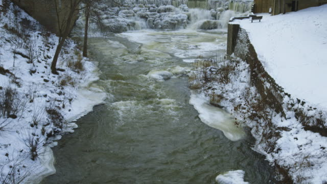 snow covered stream and waterfall, tilt up - frozen stock videos & royalty-free footage