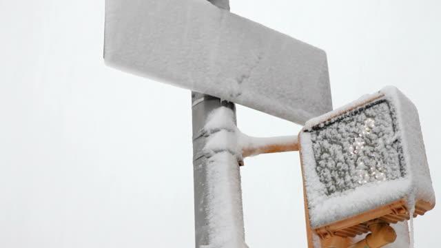 vídeos y material grabado en eventos de stock de cu la snow covered street sign and crosswalk light / new york city, new york, usa - señal de nombre de calle