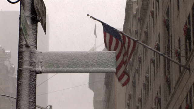 snow covered street sign with american flag blowing in background. - 旗棒点の映像素材/bロール
