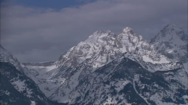 ws pan snow covered teton mountain range under cloudy winter sky / grand teton national park, wyoming, usa - teton range stock videos & royalty-free footage