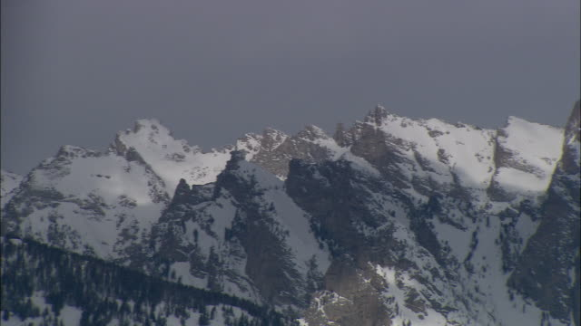 WS PAN Snow covered Teton mountain range under cloudy winter sky / Grand Teton National Park, Wyoming, USA