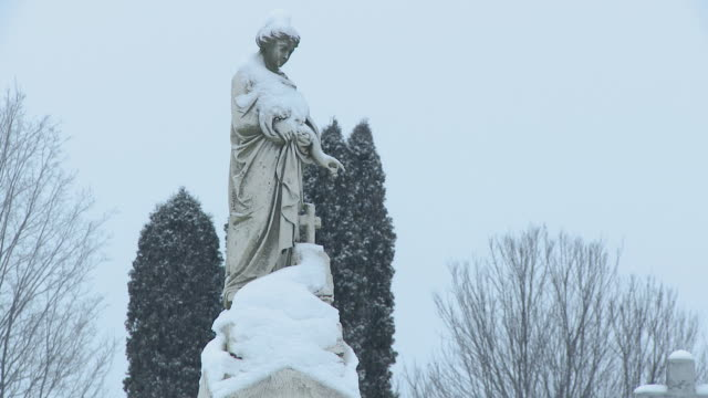 ms zo snow covered tombstone of angel in blizzard in winter evening  / ellicottville, new york, canada  - cemetery stock videos & royalty-free footage