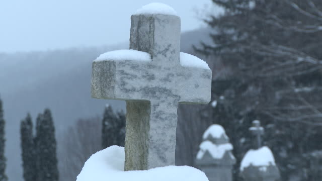 ms snow covered tombstone ( gravestone ) with cross on top in blizzard in winter day  / ellicottville, new york, canada  - gravestone stock videos & royalty-free footage