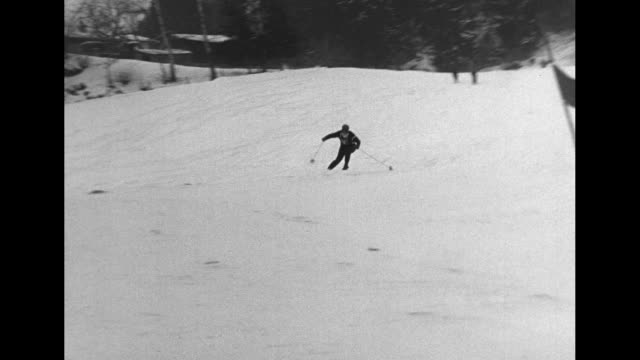 stockvideo's en b-roll-footage met snow covered town street with cars and pedestrians / #1 skier takes off down course / skier takes off down course / tall trees in bg as skier races... - documentairebeeld