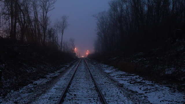 Snow covered train tracks at dusk in winter