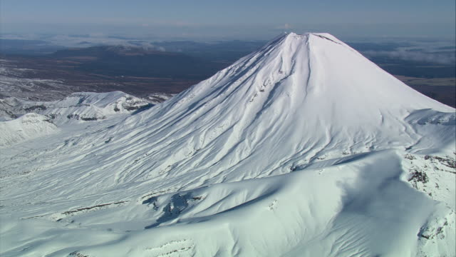aerial snow covering mount ngauruhoe and unfolding at the volcano's feet / manawatu-wanganui, new zealand - tongariro national park stock videos & royalty-free footage