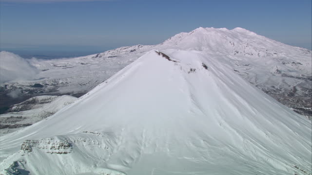 aerial snow covering mount ngauruhoe volcano, with mount ruapehu beyond / manawatu-wanganui, new zealand - tongariro national park stock videos & royalty-free footage