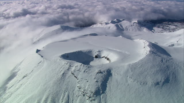 aerial snow covering the ngauruhoe cone summit crater / new zealand n the tongariro national park / manawatu-wanganui, new zealand - tongariro national park stock videos & royalty-free footage