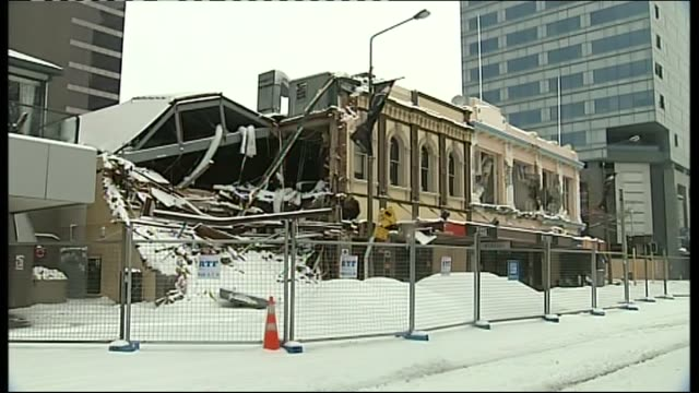 snow covering the remains of damaged buildings in christchurch's red zone area in july 2011 with damaged foreign exchange and bank buildings - カンタベリー点の映像素材/bロール