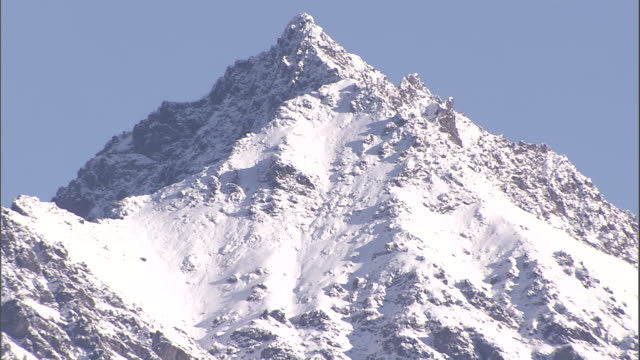 snow covers a craggy mountain peak. - crag stock videos & royalty-free footage