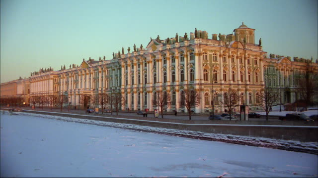 snow covers a lake near a historic building in st. petersburg, russia. - st. petersburg russia stock videos & royalty-free footage
