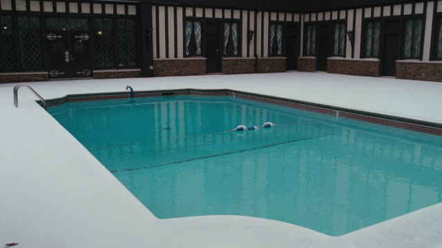 snow covers a patio around a swimming pool at a tudor style hotel. - chalet stock videos & royalty-free footage