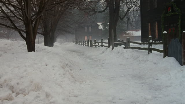 Snow covers a road along a wooden rail fence.
