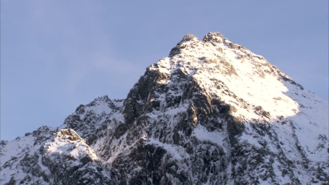 Snow covers a rocky mountain peak. Available in HD.