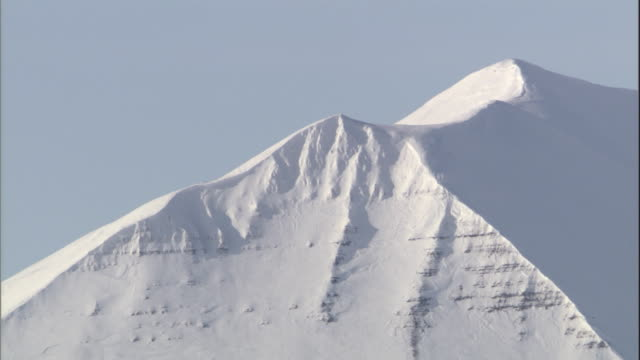 snow covers a sharp mountain ridge and cliff in svalbard, norway. - svalbard and jan mayen stock videos & royalty-free footage