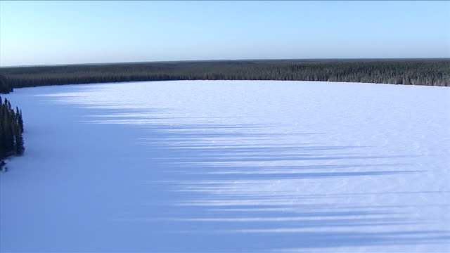 Snow covers a vast frozen lake surrounded by boreal forest, Canada. Available in HD.
