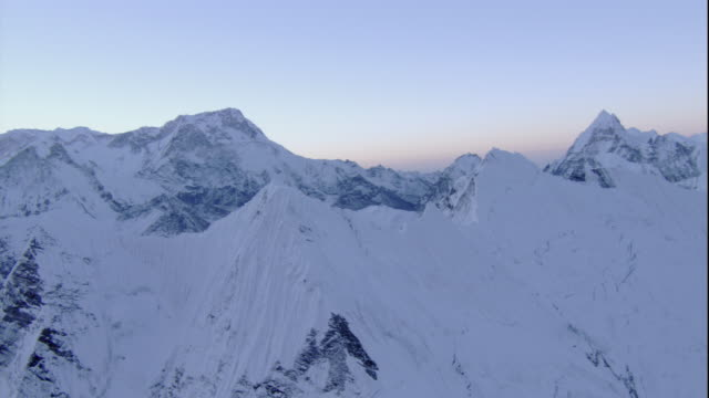 Snow covers mountain peaks in the Himalayas. Available in HD.