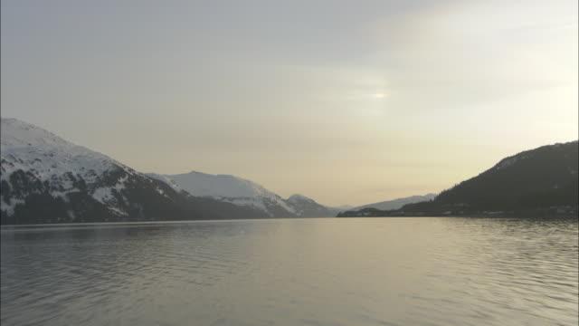 vidéos et rushes de snow covers mountains around a lake. - horizon