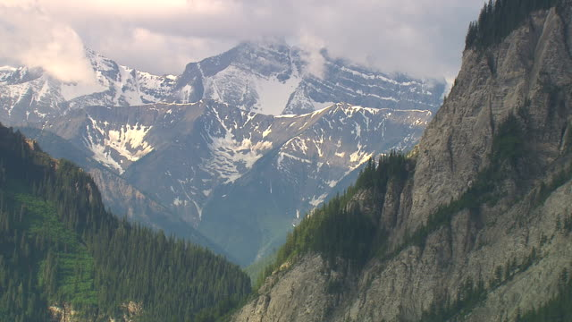 Snow covers mountains peaks along the steep Rocky Mountains range.