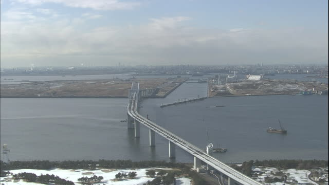 snow covers portions of the tokyo gate bridge. - ariake sea stock videos and b-roll footage