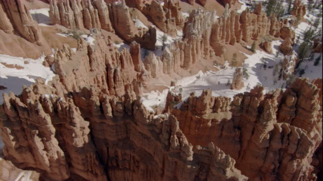 Snow covers the ground between hoodoos in Bryce Canyon. Available in HD.