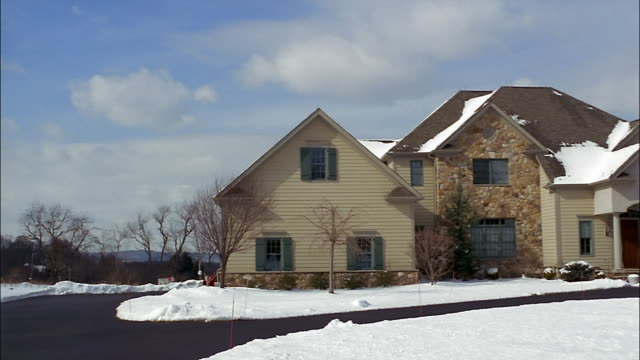 snow covers the ground in front of a large two-story suburban house in new jersey. - zweistöckiges wohnhaus stock-videos und b-roll-filmmaterial