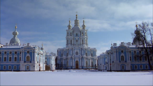 Snow covers the ground in front of historic buildings in St. Petersburg, Russia.