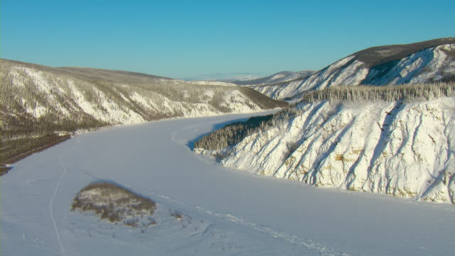 Snow covers the hills and the frozen Yukon River in Canada.