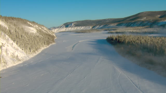 Snow covers the hills and trees along the bank of the frozen Yukon River in Canada.