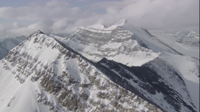 snow covers the mountain ridges of banff national park in canada. available in hd. - banff stock videos & royalty-free footage