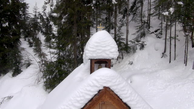 Snow covers the roof of a small chapel in the Alps.