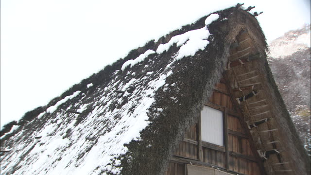 Snow covers the roof of an A-frame gassho zukuri house in Japan.